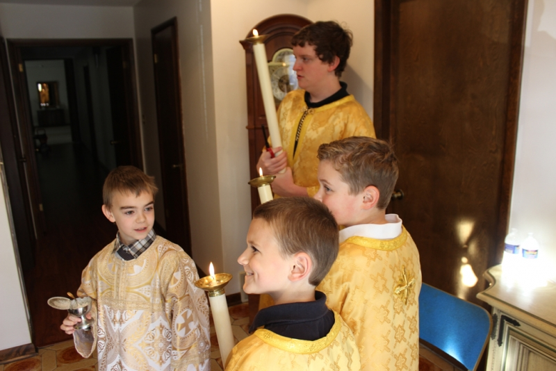 Altar boys are ready for the procession to the church